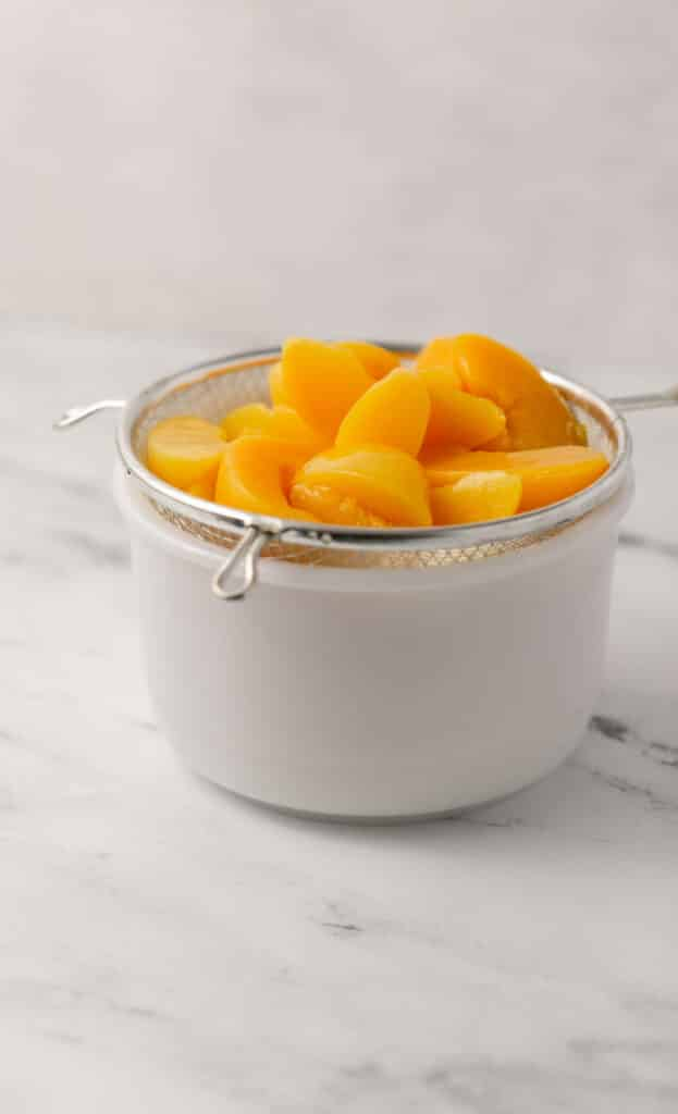 side view white bowl topped with strainer with sliced peaches in it draining