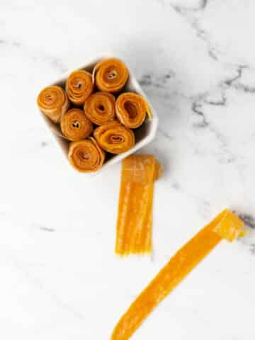 rolled up cling peach fruit leather in small square white bowl next to two unrollled pieces.