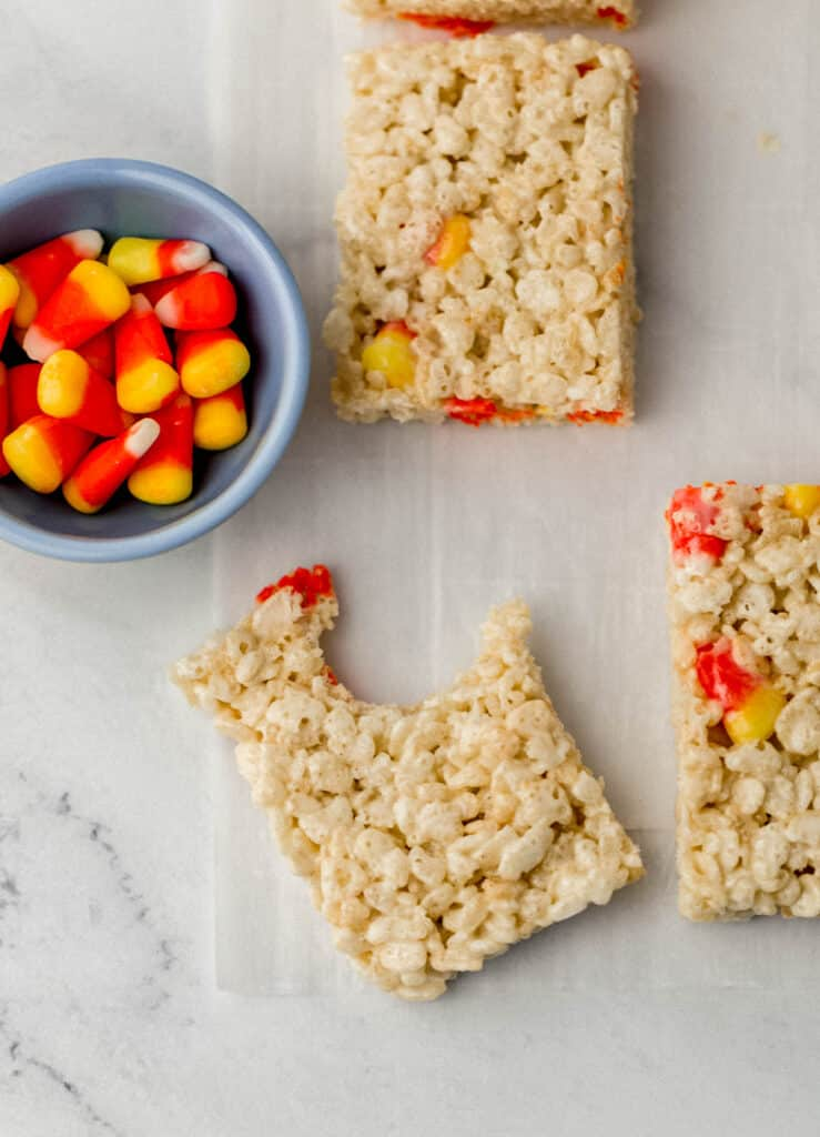 rice krispie treats and small blue bowl with candy corn in it.