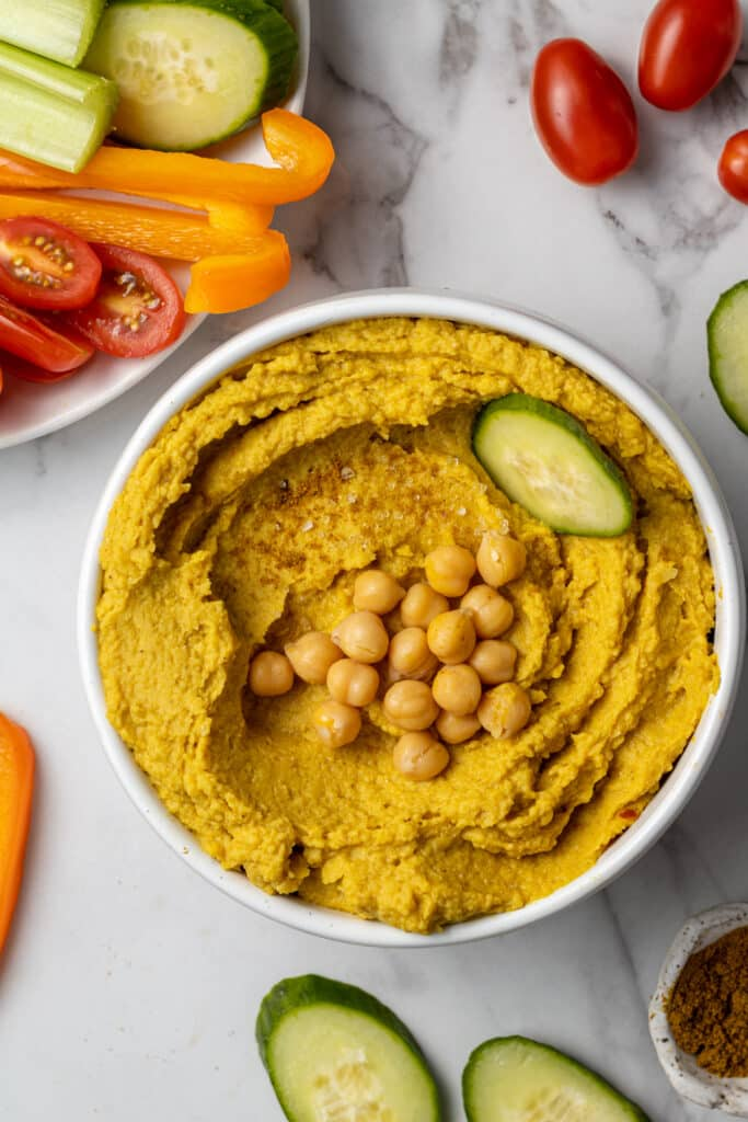 curry hummus in white bowl with vegetables