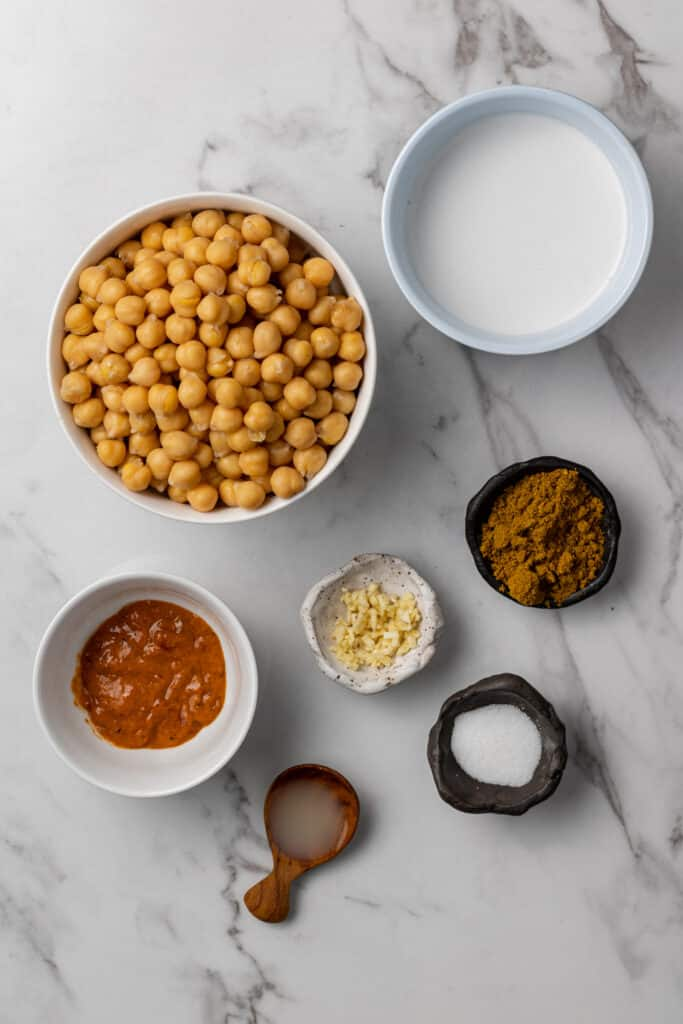 ingredients needed to make hummus on marble surface in separate bowls
