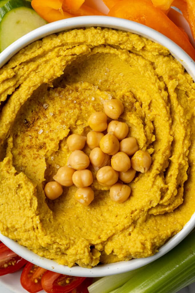 curry hummus in white bowl topped with chickpeas and salt