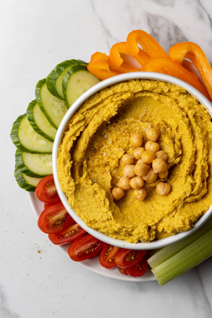 hummus in white bowl with fresh vegetables around it.