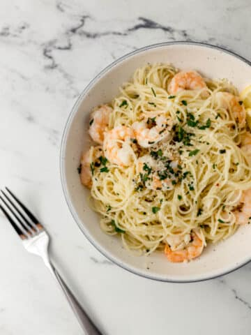 overhead view of bowl of easy shrimp scampi topped with parsley beside a fork.
