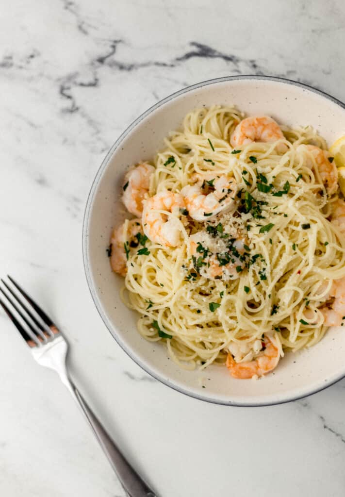 overhead bowl of easy shrimp scampi topped with parsley next to fork.