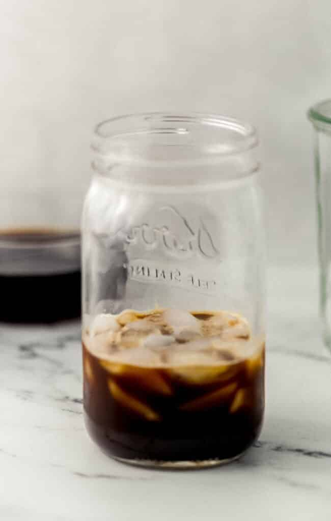 close up side view of glass jar with ice, espresso, and syrup in it.