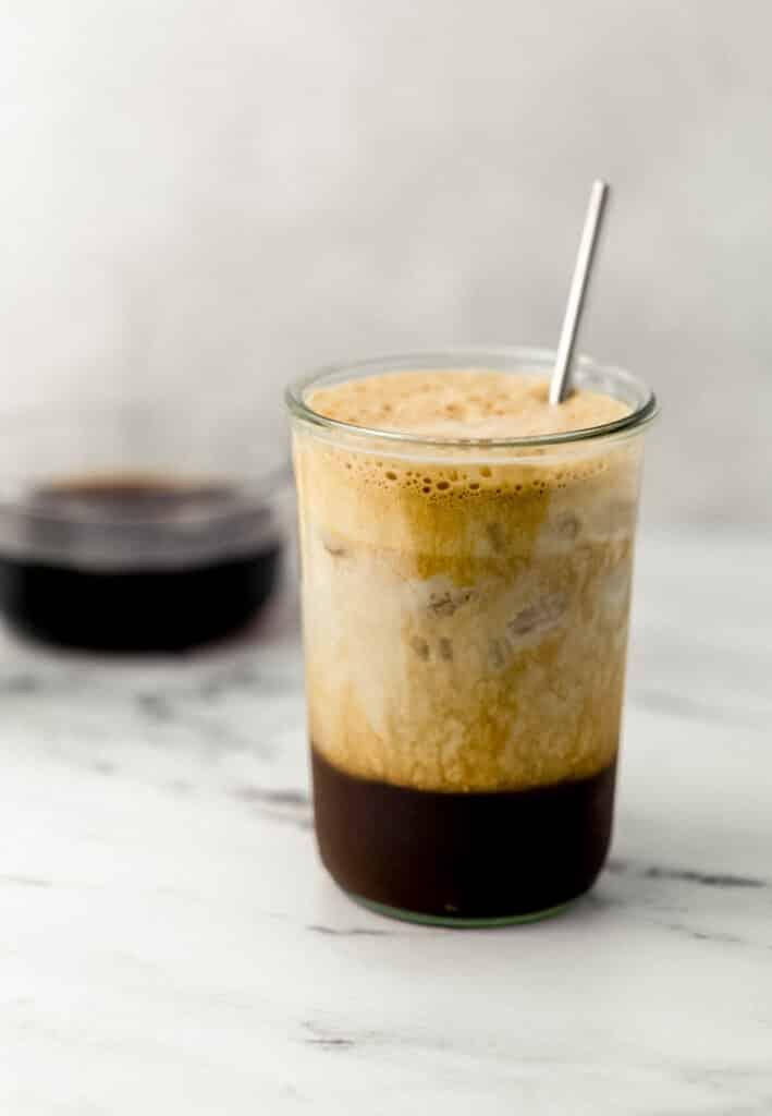 shaken espresso in glass topped with oat milk