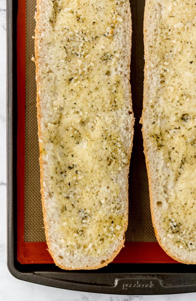 French bread on sheet pan with garlic butter sauce on it.