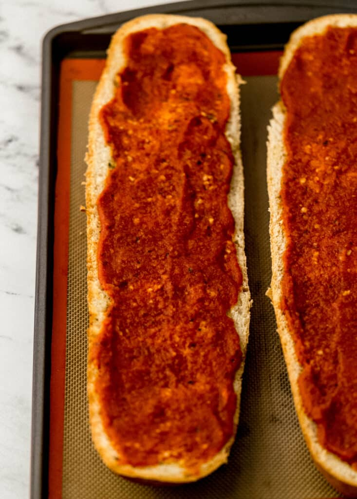 sauce spread on French bread on sheet pan