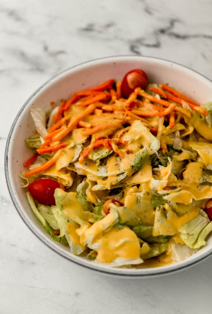 bowl of salad topped with dressing