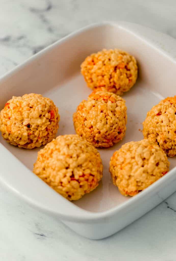 rice krispie treat mixture rolled into orange balls in white baking dish