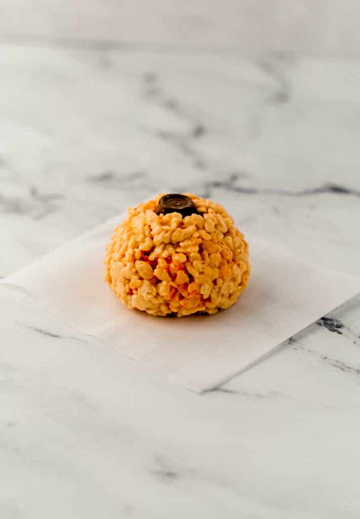 close up side view pumpkin shaped rice krispie treat with chocolate in the top